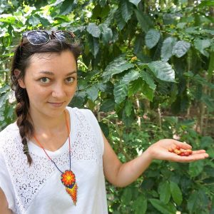 Jessica holding coffee tree fruit at a farm in Cuba